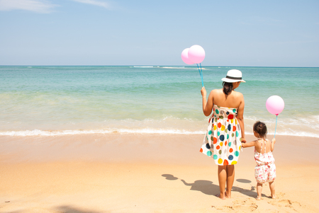 young mother and  her kid on the beach with pinky balloons