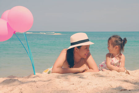Retro style young mother and  her kid on the beach with pinky balloons photo