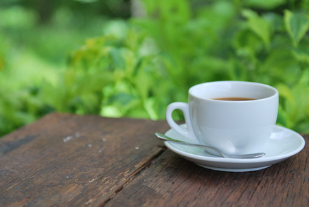 coffee cup on wood table with green  photo