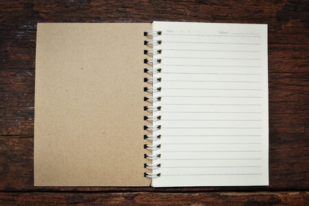 Brown notebook on a wood background photo