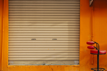 a shuttered roll up metal door with orange wall photo