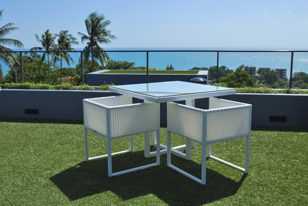 seaview: Terrace lounge with white rattan armchairs and seaview in a luxury resort .
