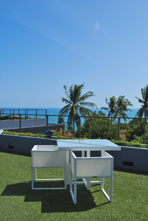 Terrace lounge with white rattan armchairs and seaview in a luxury resort . photo