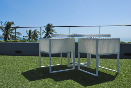 Terras lounge met witte rotan stoelen en uitzicht op zee in een luxe resort Stockfoto