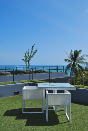 Terrace lounge with white rattan armchairs and seaview in a luxury resort   photo