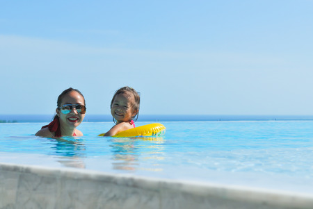 Summer vacations concept  Happy mother and daughter playing in blue water of swimming pool  photo