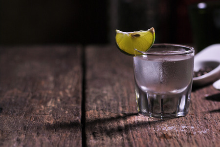 Glass of vodka shot with fresh lime on wooden table Standard-Bild