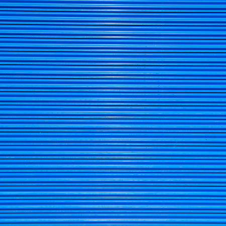 rolling garage door: a shuttered roll up metal blue door Stock Photo