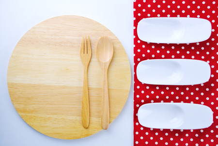 Wooden plate, tablecloth, spoon, fork on table background photo