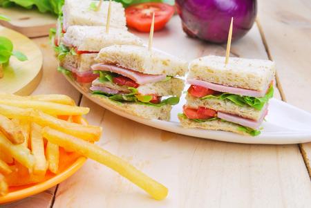 Club Sandwich met kaas, augurk, tomaat en ham. Gegarneerd met frieten