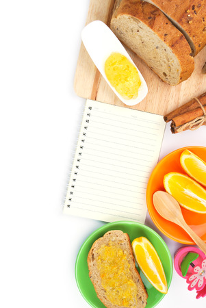 Recipe book with wholegrain bread and orange jam photo