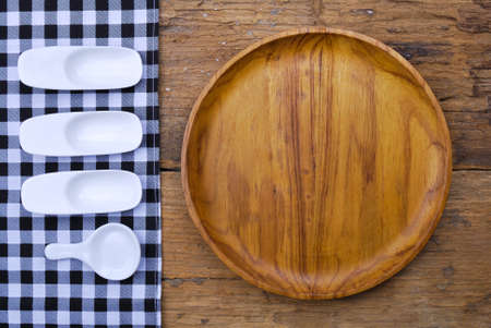 Wooden plate, tablecloth, spoon, on old table background photo
