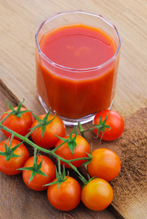 Tomato juice and  cherry tomatoes on the vine photo