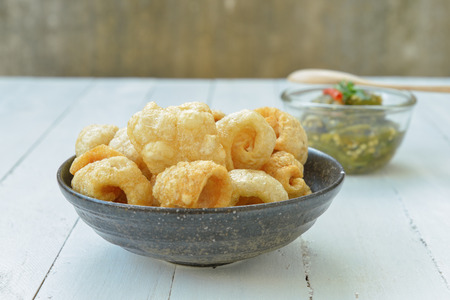 rinds: Pork rinds also known as chicharon or chicharrones, deep fried pork skin and Nam Prik Num (Northern Thai Green Chilli Dip) Stock Photo