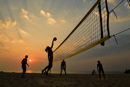 Beach volleyball silhouette at sunset , motion blurred photo