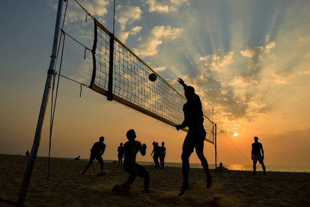 Beachvolleybal silhouet bij zonsondergang, beweging vervagen Stockfoto