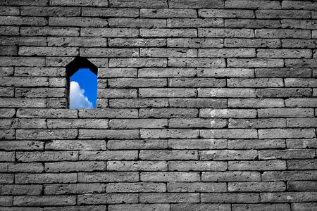 Blauwe lucht met witte wolk klein venster of gat op zwarte en witte bakstenen muur achtergrond Stockfoto