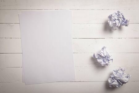 oficina desordenada: papel blanco y bolas de papel arrugado en el fondo blanco tablón de madera de color con espacio para texto