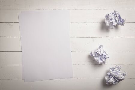 wooden desk: White paper and Crumpled paper balls on white color wood plank background with space for text