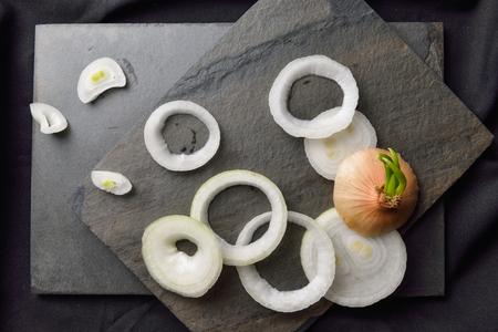 onion: Cebollas y cebollas anillos en el rock y el fondo negro