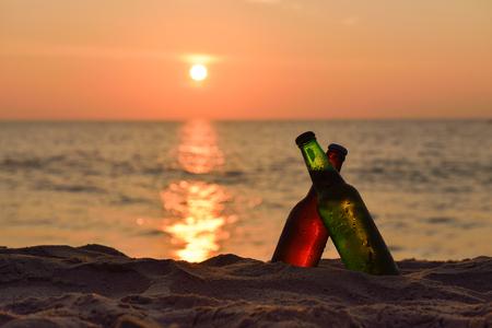 Eiskaltes braun und grün Flasche Bier am Strand bei Sonnenuntergang