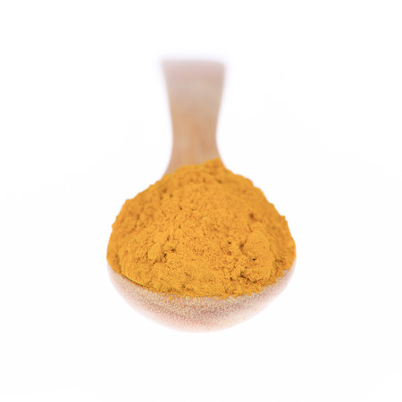 curcuma: Turmeric (Curcuma) powder on wooden spoon on white background. Stock Photo