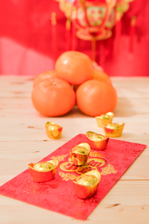 packets: mandarin oranges with Chinese new year red packets  (Foreign text means All achievements ) Stock Photo