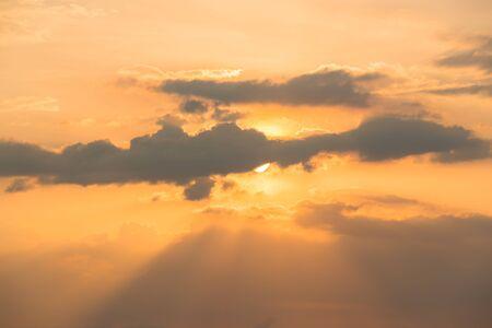 golden light: Sun and sunbeam behind clouds golden light