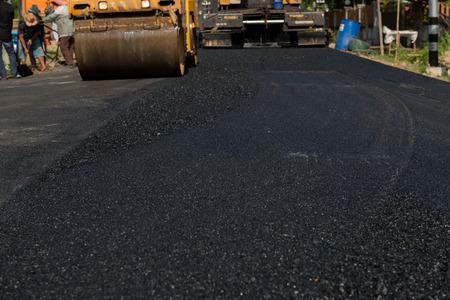 Worker operating asphalt paver machine during road construction and repairing works focus on asphalt road