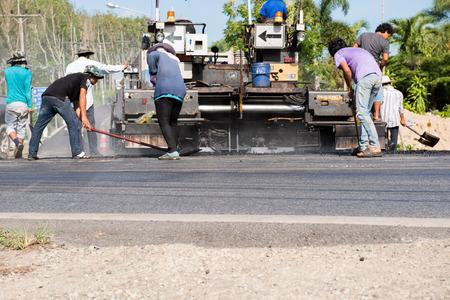paver: Worker operating asphalt paver machine during road construction and repairing works focus on asphalt road