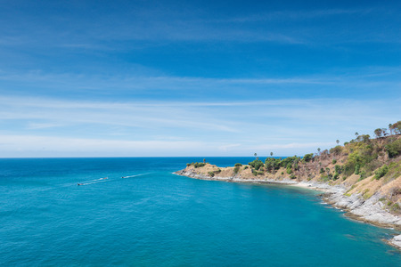 sea scene: View of the rocky cliffs boat sailboat and clear sea under the bright sun. Promthep cape. Viewpoint in Phuket Thailand