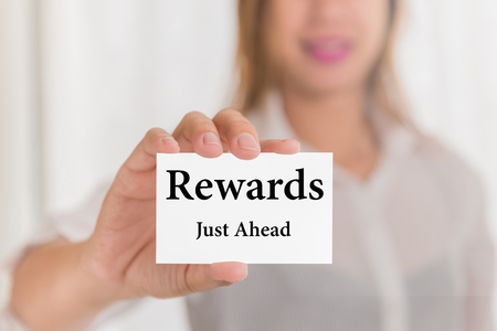 rewards card: Rewards just ahead message word on card in hand of Friendly woman hand and smiling Stock Photo