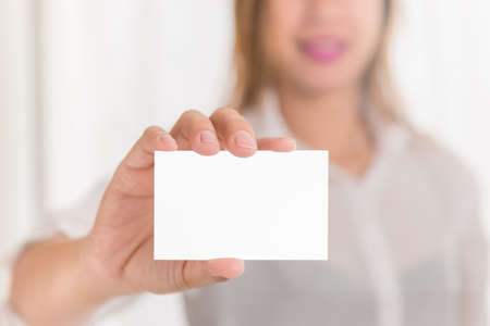 businessperson: Friendly woman holding a business card and smiling