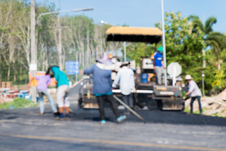 vibration machine: Blurred Worker operating asphalt paver machine during road construction and repairing works