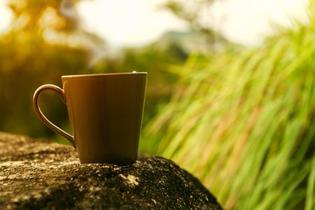 coffee mug on rock table in morning sunrise or sunset Stock Photo