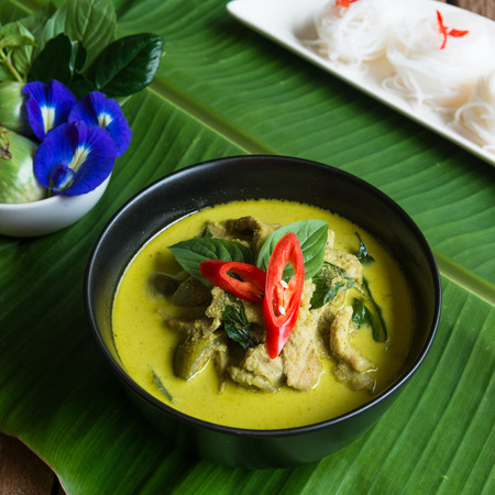 favorite soup: Green curry creamy coconut milk with chicken with thai rice noodle , the Popular Thai food called Kanom jeen , Gaeng Keow Wan Gai on wooden table Stock Photo