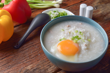 Thai chinese asian rice porridge with pork and egg in bowl, congee