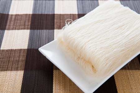 Close-up of white rice noodles on a white plate. rice vermicelli.