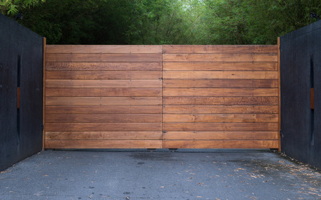 Sliding driveway door with iron and wooden panel and black wall Stock Photo