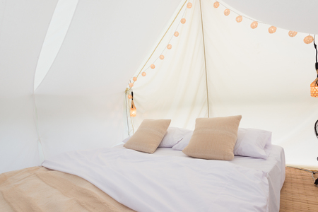 furnishings: Inside a large white tent camp with bed and interior furnishings Stock Photo