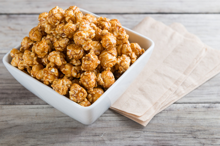 Caramel popcorn on wooden table background