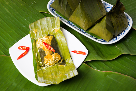 steamed fish with curry paste in banana leaf Stock Photo