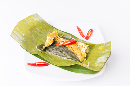 steamed fish with curry paste in banana leaf on white table Stock Photo