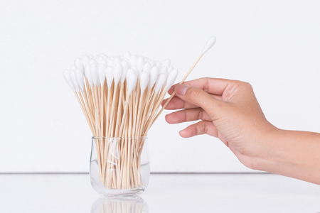 Cotton bud wood stick or cotton swab on background with hand