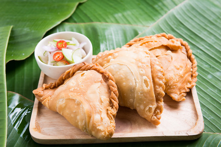 curry puff stuffed chicken on banana leaf background Stock Photo
