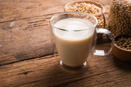 Glass with Soy Milk and Seeds on wooden background