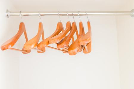 Empty wooden hangers in wardrobe