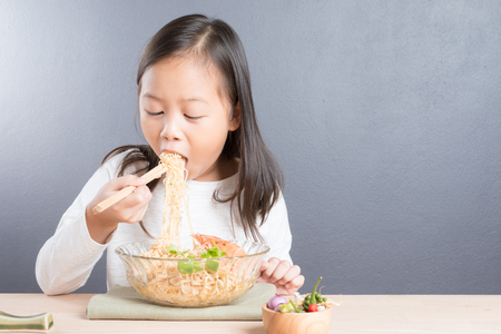 Happy Asian child age 6 years eating delicious noodle with chopsticks in glass bowl