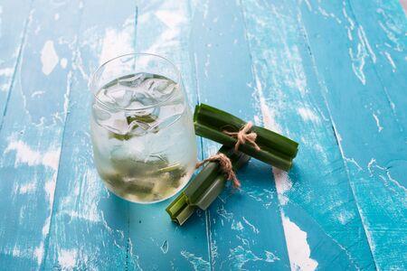 Fresh Fragrant Pandan Ice Tea  and leaves on green wood background