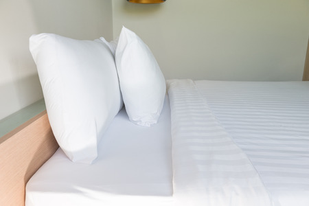 bedside: White pillow and white bed in bed room for clean and comfort sleep Stock Photo